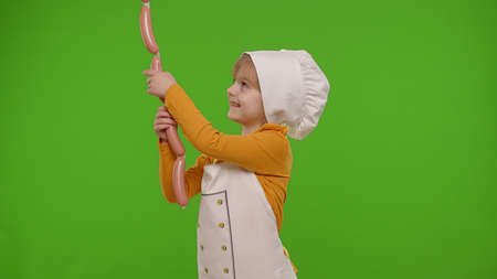 Child girl kid dressed as cook chef taking sausages from above, fooling around, making faces, putting around her neck on chroma key background. Nutrition, cooking food school, education. Fun and humor 版權商用圖片