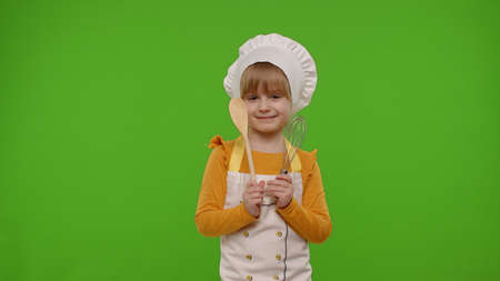 Child girl kid dressed as professional cook chef baker posing, smiling, looking at camera on chroma key background. Copy-space. Nutrition, cooking school, education, food. Fun and humor. Restaurant