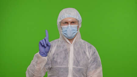 Confident doctor in PPE protective suit disapproving showing warning dangerous no sign on chroma key background. Rejecting, asking to stop, make negation finger gesture, denying, disagree. Copy-space