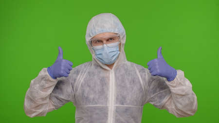 Medical doctor in PPE protective suit showing thumbs up sign, like gesture, demonstrating approval, feeling enthusiastic satisfied with excellent result.