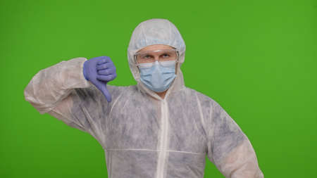 Dissatisfied doctor in PPE protective suit disapproving, pointing fingers down, showing thumbs down gesture say no, dislike with bad results