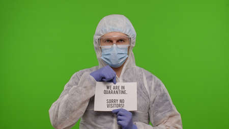 Medical worker doctor in PPE suit with text inscription slogan on paper