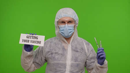 Medical worker doctor in PPE suit with syringe, ampoule and text slogan on paper