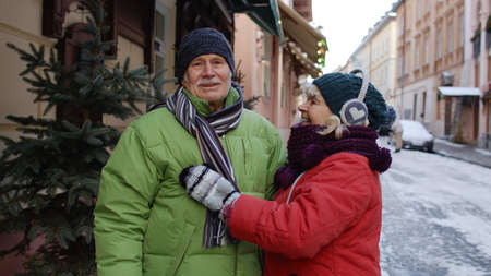 Senior couple grandmother and grandfather tourists in colorful winter jackets walking, talking, gesturing on city street in town Lviv, Ukraine. Elderly family man, woman on holidays vacation traveling