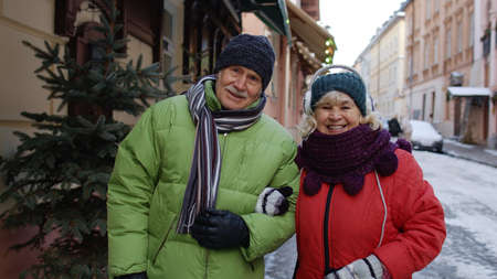 Front view of senior couple tourists man and woman walking, talking, gesturing on winter holiday city street. Elderly grandmother, grandfather enjoying conversation, traveling together. Mature family 版權商用圖片