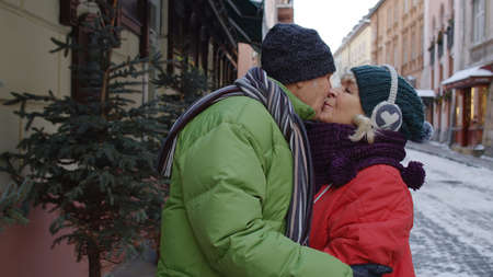 Portrait of stylish senior elderly couple tourists grandmother and grandfather walking, traveling, hugging, embracing, making a kiss in winter city holidays vacation. Lovely mature pensioners family