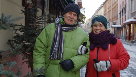Portrait of stylish senior elderly couple tourists grandmother and grandfather walking, traveling, hugging, embracing in winter city holidays vacation. Lovely mature pensioners family 版權商用圖片