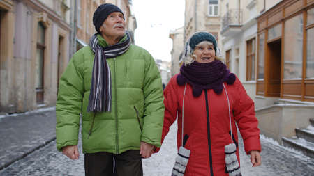 Senior old couple tourists man woman walking, talking, gesturing on winter snowy city Lviv, Ukraine street. Elderly grandmother, grandfather enjoying conversation, traveling together. Mature family