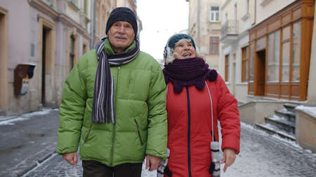 Senior couple tourists man and woman walking along street in winter snowy town Lviv, Ukraine. Elderly grandmother, grandfather holding hands talking enjoying time together, trip vacation