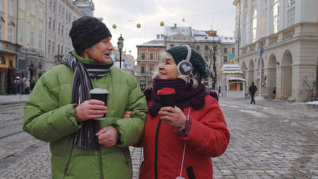 Stylish senior couple tourists grandmother grandfather traveling, drinking from plastic cups, enjoying hot drink tea, coffee in winter city center. Elderly pensioners family Christmas vacations