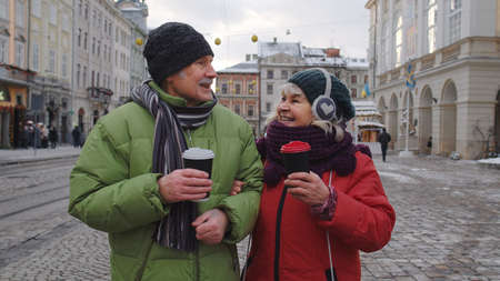 Senior wife and husband tourists drinking from cups, enjoying hot drink tea, coffee on winter city central street in Lviv, Ukraine. Family man and woman vacation trip activities. Life after retirement 版權商用圖片
