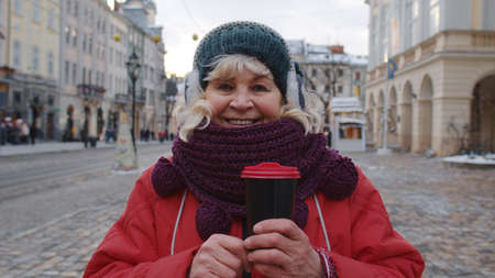 Portrait of stylish senior woman tourist smiling, looking at camera in winter city center of Lviv, Ukraine. Travelling, vacation, trip, Christmas holidays eve concept. Active life after retirement