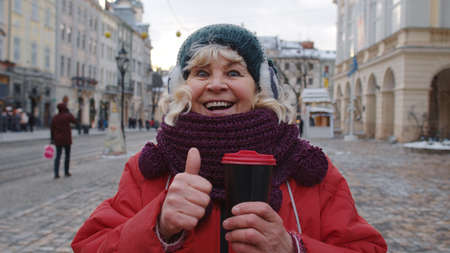 Senior woman grandmother smiling, showing thumb up in winter city center of Lviv, Ukraine. Travelling, vacation, trip, Christmas holidays eve. Active life after retirement during lockdown 版權商用圖片