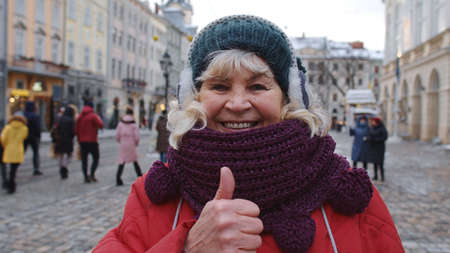 Portrait of stylish senior woman tourist smiling, showing thumb up, looking at camera in winter city center of Lviv, Ukraine. Photography, travelling, vacation. Active pensioners life after retirement