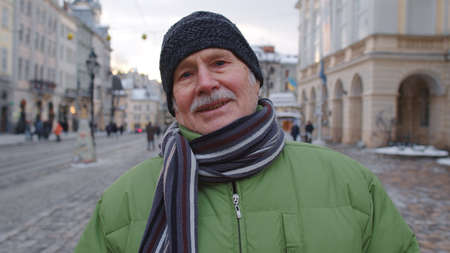 Portrait of stylish senior man grandfather tourist smiling, looking at camera in winter city center of Lviv, Ukraine. Travelling, vacation, Christmas holidays eve concept. Active life after retirement