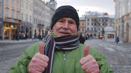 Senior man grandfather smiling, showing thumbs up in winter city center of Lviv, Ukraine. Travelling, vacation, trip, Christmas holidays eve. Active life after retirement during lockdown 版權商用圖片