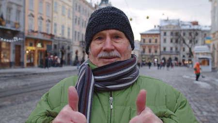 Portrait of stylish senior man tourist smiling, showing thumbs up, looking at camera in winter city center of Lviv, Ukraine. Photography, travelling, vacation. Active pensioners life after retirement 版權商用圖片
