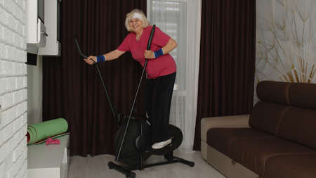 Senior elderly caucasian woman in sportswear using orbiter in room at home doing sport training warming up cardio exercises. Active old grandmother during lockdown. Healthy lifestyle