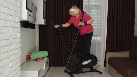Old grey-haired senior grandmother model exercising workout on orbitrek in room at home. Retro style Caucasian mature elderly woman warming up while sitting on orbitrek indoor. Healthy sport lifestyle