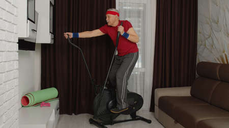 Senior elderly caucasian man in sportswear using orbitrek in living room doing sport training warming up cardio exercises at home. Active old grandfather during lockdown. Healthy lifestyle 版權商用圖片