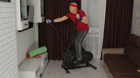 Senior mature man in sportswear using orbitrek in living room at home. Online learning and study active healthy lifestyle sporty old male person training cardio workout wellness and indoors exercising