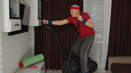 Senior man using orbitrek with vitality exercises in living room. Old pensioner grandfather training healthcare sport at home, fitness exercising workout at elderly age during quarantine