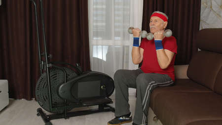 Old grey-haired senior grandfather model doing weight lifting dumbbells exercises in room at home. Retro style Caucasian mature elderly man warming up while sitting on sofa. Healthy sport lifestyle