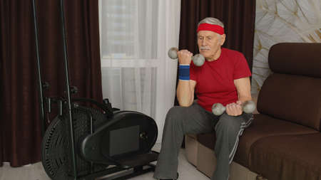 Senior elderly caucasian man in sportswear doing weight lifting dumbbells exercising in room sport training warming up cardio exercises at home. Active old grandfather during lockdown 版權商用圖片