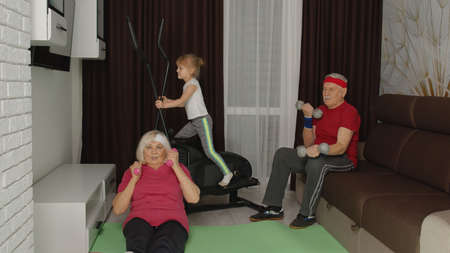 Senior mature grandfather, grandmother, granddaughter in sportswear using orbitrek, doing weight lifting, stretching sport dumbbells exercises in living room at home. Workout of sporty old people