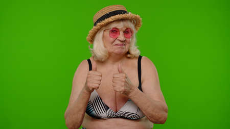 Elderly woman tourist in swimsuit and sunglasses, looking at camera, smiling, showing thumbs up