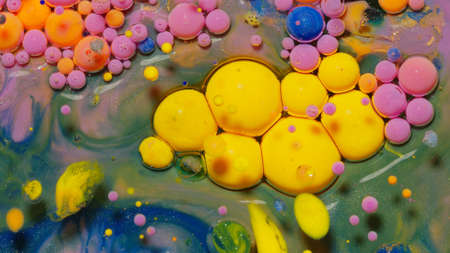 Yellow neon colorful bubbles oil and ink, beautiful fluorescent paint. Sparkling color multicolor moving close-up. Acrylic painting. Themes or wallpaper background. Abstract transformation gravitation