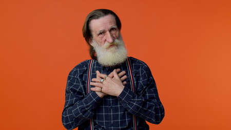 Confused senior old bearded gray-haired man pointing fingers himself ask say who me no thanks i do not need it isolated on orange studio background. Elderly grandfather pensioner. I am not guilty