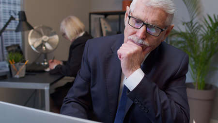 Thoughtful senior professional businessman grandfather director working on laptop inside office pondering and imagining in mind, wondering difficult solution, feeling confused, not sure about choice.