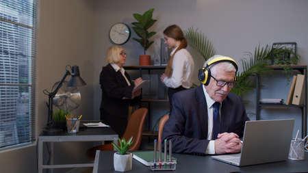 Happy business man entrepreneur working on laptop listening music on headphones. Senior old male professional using computer at office. Freelancer working on modern tech notebook device Standard-Bild
