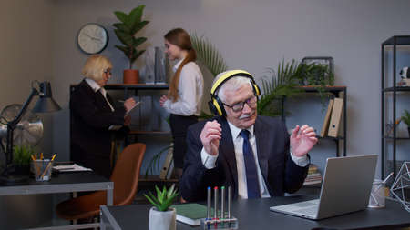 Cheerful senior business company manager working on portable laptop sitting at desk, listening music and dancing. Mature businessman in office interior. Coworking, cooperation. Freelance business