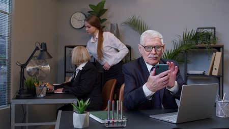 Senior professional businessman grandfather company director in modern office interior using mobile phone texing message working watching video successful people communicating. Elderly freelancer man Standard-Bild