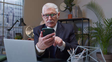 Senior professional businessman grandfather company director in modern office interior using smartphone texting checking email messages online successful male executive at work. Elderly freelancer man