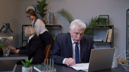 Elderly old businessman checking corporate paperwork correspondence at office, shocked surprised, disbelief. Senior entrepreneur reading documents, analyzing financial papers, preparing audit report