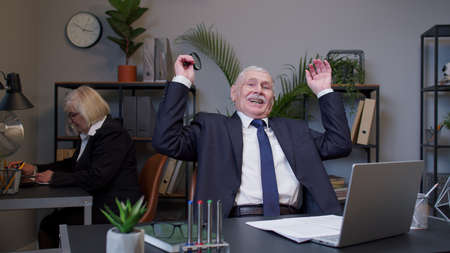 Senior old business man accountant reading documents, analyzing financial papers, preparing audit report at office workplace, raising hands in surprise looking at camera shocked by sudden victory Standard-Bild