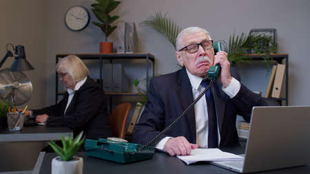 Annoyed senior old businessman grandfather executive talking loudly on retro telephone call irritated voice dissatisfied with work arguing at office table workspace. Elderly mature freelancer boss man