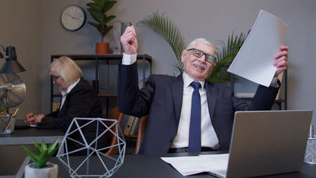 Mature elderly business man accountant reading documents, analyzing financial papers, preparing audit report at office workplace, raising hands in surprise looking at camera shocked by sudden victory