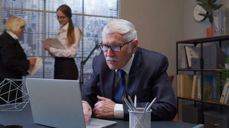 Elderly man boss working in modern office room interior. Senior entrepreneur freelancer concentrated developing new project while working, typing on laptop computer. Portrait of businessman co-worker Standard-Bild