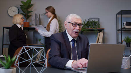 Excited senior business company manager working on portable laptop sitting at desk. Mature old businessman celebrating sudden victory with colleagues in office. Coworking, cooperation