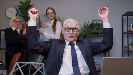 Excited senior business company manager working on portable laptop sitting at desk. Mature old businessman raising hands celebrating sudden victory with colleagues in office. Coworking, cooperation