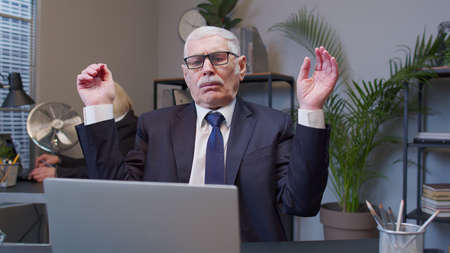 Tired disappointed old business man using laptop sit at office workplace. Senior sad male manager showing aggressive upset emotion after unsuccessful online deal with client. Coworking. Freelance