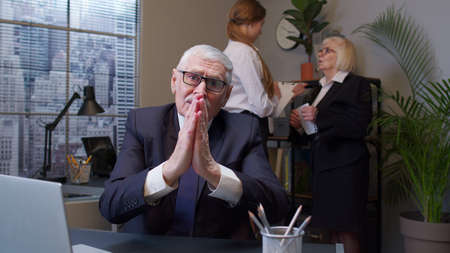 Elderly man boss pleading expression, begging apology, beseeching with hopeful face in office. Senior entrepreneur freelancer keeping prayer gesture and asking help. Portrait of businessman co-worker