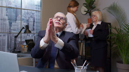 Mature elderly freelancer man praying to God, looking upward and making wish good luck in office. Senior businessman grandfather company director having debt problems, financial crisis, bankruptcy.