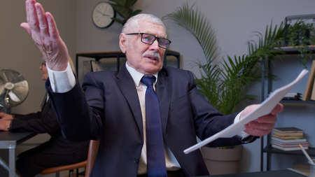 Irritated elderly man boss raising hands in questioning gesture why what in office room. Mature entrepreneur freelancer dissatisfied with bad results of work reviewing report and documents with errors Standard-Bild