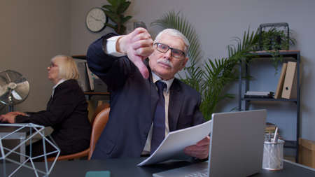Unhappy elderly man boss making thumbs down gesture expressing discontent, disapproval in office room. Senior freelancer dissatisfied with bad results of work reviewing report, documents with errors