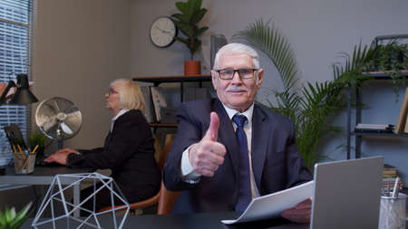 Cheerful senior company manager showing thumbs up approval gesture. Mature businessman accountant satisfied with good results of work reviewing report, documents in office. Coworking, cooperation